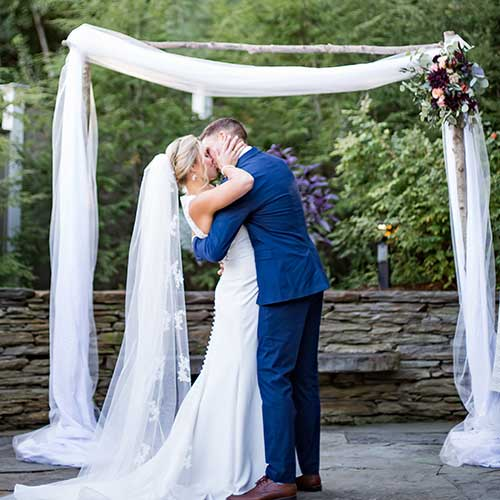 Bride and Groom Kissing by Outdoor Wedding Arbor